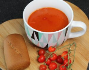 simple tomato and basil soup in a large cup/bowl on a chopping board with small tomatoes on the vine in front and a bread roll to the side