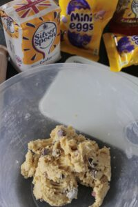 The Mini Egg Cookie Bar dough in a mixing bowl with some of the ingredients behind
