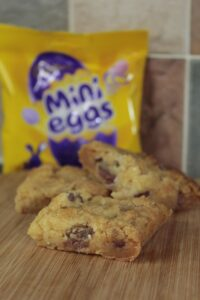 Mini Egg Cookie Bar cut up and sitting stacked on a wooden board. A pack of Mini Eggs can be seen in the background